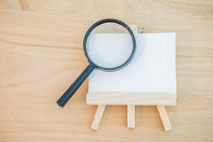 White canvas art board with magnifier glass Stock Image