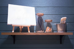 White canvas with paint brushes and pencils on the shelf Stock Photo