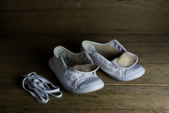 White canvas shoes on wood background, still life Stock Image