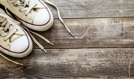 White canvas shoes on wooden background. Copy space. stock photo