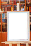 White canvas of simple picture frame on easel in library Royalty Free Stock Image