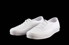 White canvas sneakers isolated on black Stock Photos