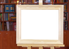 White canvas of wide wood picture frame on easel. With clipping path and home library on background Royalty Free Stock Images
