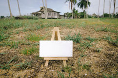 White canvas on wooden easel over village background Royalty Free Stock Photography