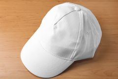 White cap for branding. On wooden background stock photography
