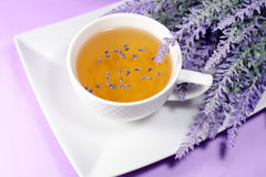 White cap with lavender tea. White porcelain cup with natural lavender tea, flowers branch against violet linen background royalty free stock photos
