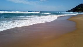 Pacific Ocean Waves on NSW South Coast Beach, Australia. White capped Pacific Ocean waves rolling onto the yellow sand Stanwell Park Beach, NSW South Coast stock footage