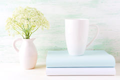 White cappuccino mug mockup with wild meadow flowers in pitcher Stock Images