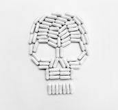 White capsules forming a skull symbol on gray background. Top view, copy space, high resolution product. Drug abuse concept Royalty Free Stock Photography