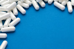 White capsules medications on blue background. Royalty Free Stock Photos