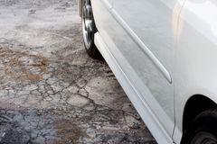 Beside of white car. ฺBeside of white car stop on crack of cement floor royalty free stock image