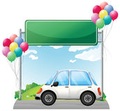 A white car along the road with balloons and a green signage Royalty Free Stock Photography