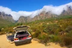 White car and amazing mountains. Covered by snow white cloud. Shot in Hottentots Holland Mountains, Vergelegen area, near Somerset West, Western Cape, South Stock Image