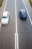 White car and black car in passing. Cars in motion on the asphalt road Royalty Free Stock Image