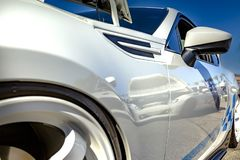 White car with blue strips and white rims closeup shot from the Stock Photography