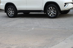 White car on concrete road. Lower part of white car on concrete road Stock Photos