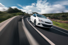 White car cornering in mountain road Royalty Free Stock Images
