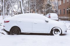 White car covered with snow parked near the house. Snowstorm fell asleep car royalty free stock images