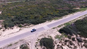 A white car is driving along the road in the desert. stock footage
