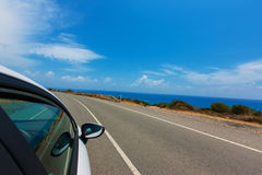 3.white car driving by autobahn on the coast of the Mediterrane. White car driving by road on the coast of the Mediterranean Sea,Cyprus in with motion blur Stock Image