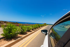 White car driving by autobahn on the coast of the Mediterranean. White car driving by road on the coast of the Mediterranean Sea,Cyprus in with motion blur Stock Photography