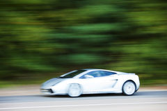 White car driving fast on country road Stock Photo