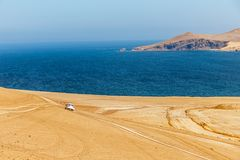 White car driving through Paracas desert toward the blue waters. Of Pacific ocean, Paracas, Peru Stock Image