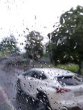 White car driving in the rain. SUV vehicle driving in the rain from behind a wet glass Royalty Free Stock Photos