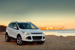 White car fast drive at stone coast. At sunset royalty free stock photo