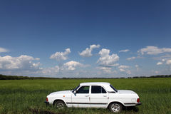 White car. In the field under white clouds Royalty Free Stock Images