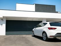 White car in front the house with garage door Royalty Free Stock Images