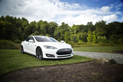 White Car on Green Grass Sorrounded by Trees Under White Clouds Stock Photos