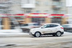 The white car at high speed. Flying on the machine speed zasnezhannoy city road Stock Photo