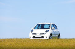 White car on a hill. New white car parked on a hill against a blue sky in this green / eco friendly transport concept Stock Image