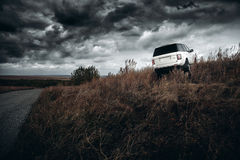 White car Land Rover Range Rover stand on countryside off-road at dramatic clouds daytime Stock Photos