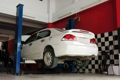 A white car is lifted up for the repairing process at the garage stock photos