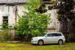 White Car Mitsubishi Airtrek Outlander Parked Near Abandoned Shabby Building, Royalty Free Stock Images