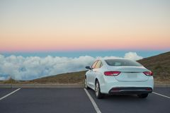 White car in mountains above the clouds at sunset or sunrise Stock Photo