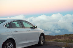 White car in mountains above the clouds at sunset or sunrise Royalty Free Stock Photos