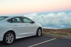 White car in mountains above the clouds at sunset or sunrise Stock Photography
