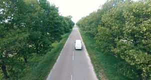 White car moving fast on two lane road in forest, above view. White car moving fast on two lane road in forest stock footage