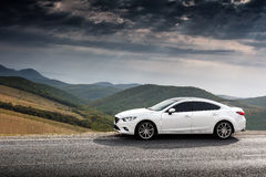 White car parked at countryside asphalt road near green mountains. At daytime Stock Photo