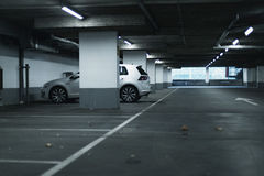 White car parked in empty parking garage. Royalty Free Stock Image