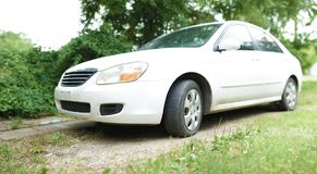 White car parked in grass - wide angle royalty free stock photos