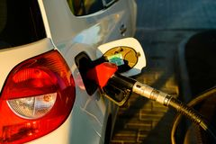Car fueling petrol at station. White car at petrol station being filled with petrol royalty free stock images