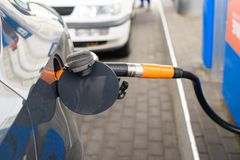 Car fueling petrol at station. White car at petrol station being filled with petrol stock image