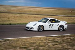 Car racing on track. White car racing on rural track on sunny day Stock Photos