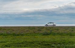 White car on a road against a background of green grass, sea and cloudy sky. White car on a straight road against a background of green grass, sea and cloudy sky Stock Photo
