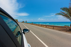 White car on the road along the coast of the Mediterranean Sea w. Car on the road along the coast of the Mediterranean Sea with motion blur background Royalty Free Stock Photos