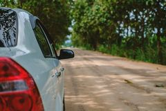 White car on long rural road amidst green trees Stock Photo